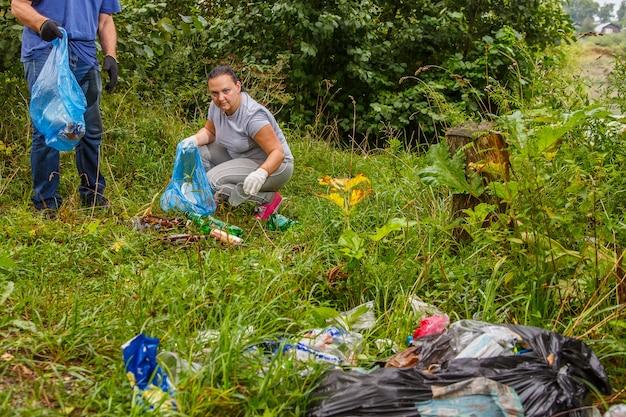 Wolontariusze usuwają śmieci ze składowiska w naturze. zdjęcie poziome