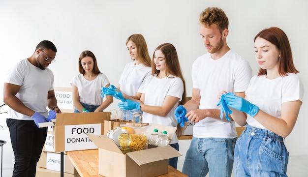 Wolontariusze w rękawiczkach przygotowują jedzenie do darowizny