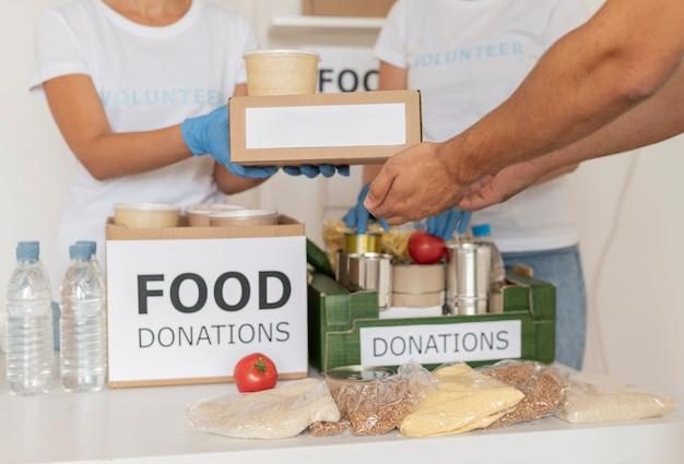 Wolontariusze w rękawiczkach rozdają pudełka z prowiantem na darowiznę