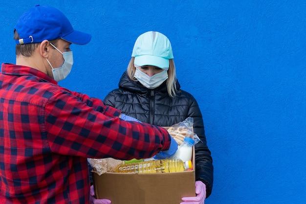 Wolontariusze z paczką charytatywną na niebieskim tle