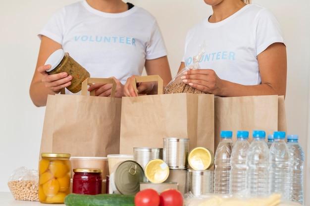 Wolontariusze z torbami prowiantu i wodą do darowizny