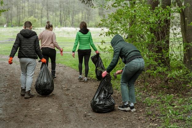 Wolontariusze z workami na śmieci na wycieczce do natury, oczyszczają środowisko.