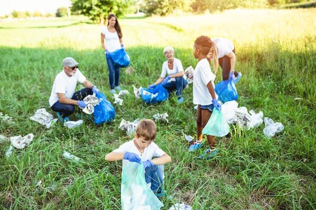 Wolontariusze z workami na śmieci sprzątanie śmieci na zewnątrz - koncepcja ekologii.