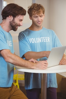 Wolontariusze za pomocą laptopa
