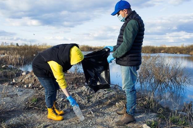 Wolontariusze zbierają plastikowe butelki w workach na brzegu rzeki, koncepcja ekologii i ochrony ziemi.