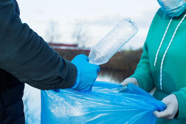 Wolontariusze zbierają plastikowe butelki w workach, zbliżenie dłoni, pojęcie ekologii i ochrony ziemi.