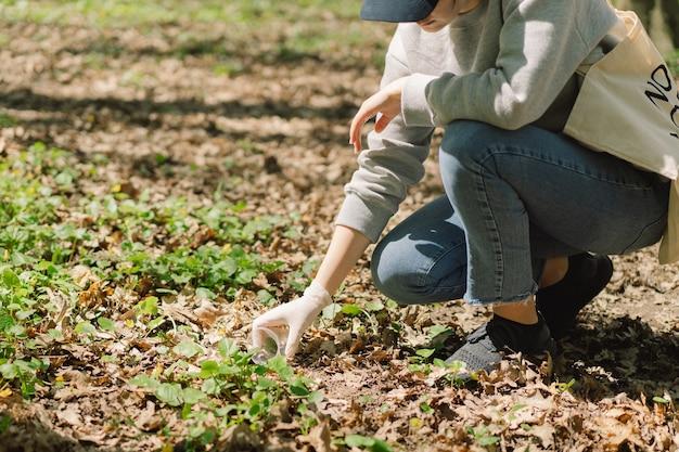 Wolontariuszka oczyszcza się w lesie kobieta zbiera plastik
