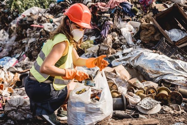 Wolontariuszka pomaga wyczyścić pole plastikowych śmieci. dzień ziemi i ekologia.