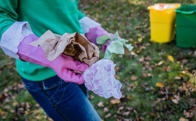 Wolontariuszka sortuje śmieci na ulicy w parku. pojęcie recyklingu.