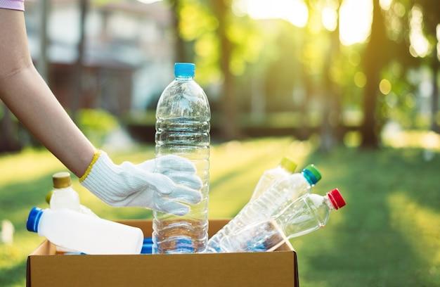 Wolontariuszka trzyma plastikową butelkę w papierowym pudełku w publicznym parku, utylizacja koncepcji recyklingu i zarządzania odpadami, dobry świadomy umysł