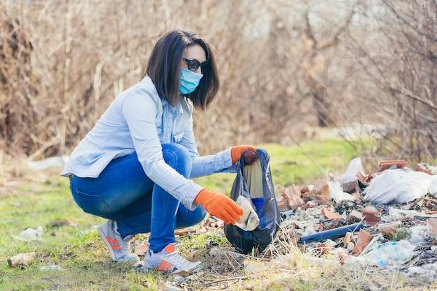 Wolontariuszka trzyma torbę z zebranym plastikiem, sprzątając las i park ze śmieci