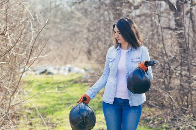 Wolontariuszka trzyma torby z zebranym plastikiem, sprzątając las i park ze śmieci