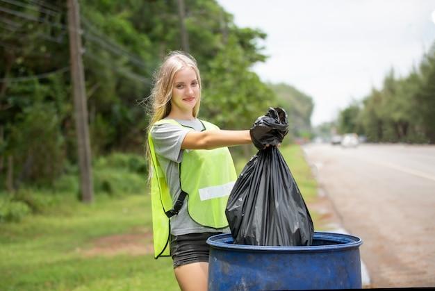 Wolontariuszka trzymająca plastikowy worek na śmieci, zbierająca śmieci i umieszczająca je w czarnym worku na śmieci.