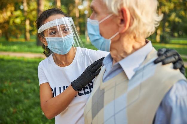 Wolontariuszka w białej koszuli patrząca na starszego mężczyznę na zewnątrz