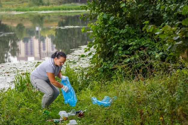 Wolontariuszka wywozi śmieci ze składowiska w pobliżu rzeki.