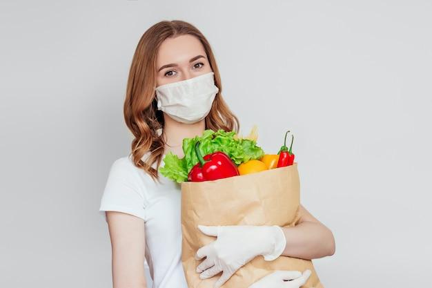 Wolontariuszka yound kobieta w masce medycznej trzyma papierową torbę z produktami, warzywami, papryką, sałatką na białym, białym, szarym miejscu, dostawa żywności