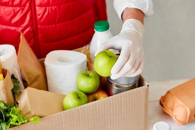 Wolontariuszka z rękawiczkami chirurgicznymi wkładająca żywność do pudełka na datki