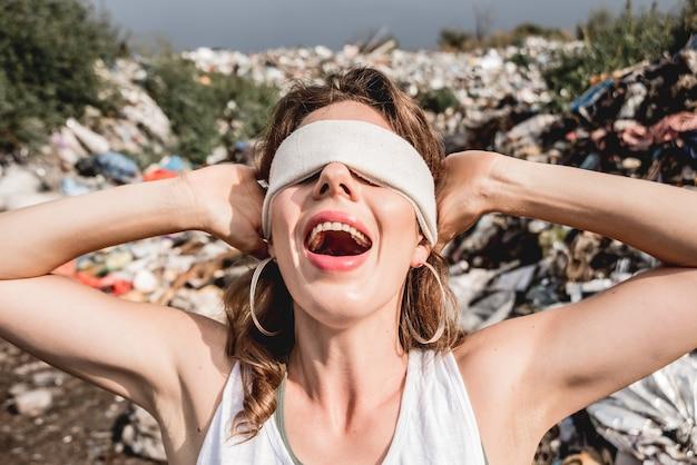 Wolontariuszka z zasłoniętymi oczami krzyczy z bezsilności na wysypisku plastiku