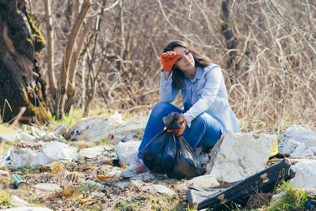 Wolontariuszka zmęczona zbieraniem plastiku z lasu i parku ze śmieci