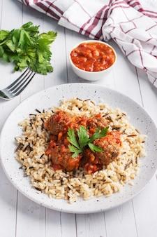 Wołowe klopsiki i brązowy ryż na talerzu.