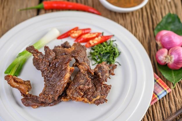 Wołowe smażone tajskie jedzenie na białym talerzu z wiosenną cebulą, liśćmi limonki kaffir, chilli, czerwoną cebulą i pomidorami.