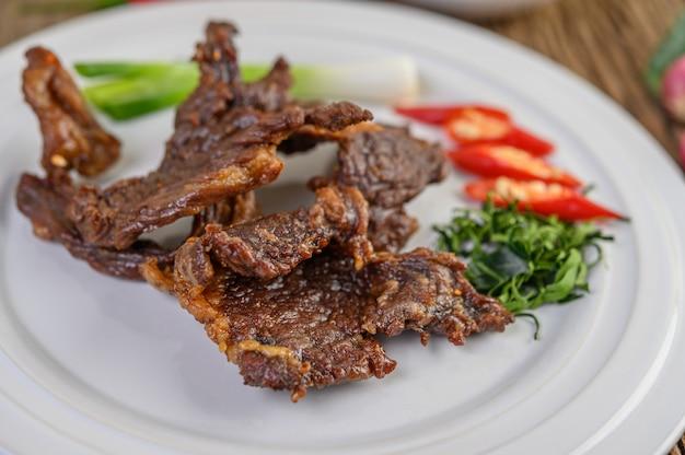 Wołowe smażone tajskie jedzenie na białym talerzu z wiosenną cebulą, liśćmi limonki kaffir, chilli, sałatką i pastą chili w filiżance.