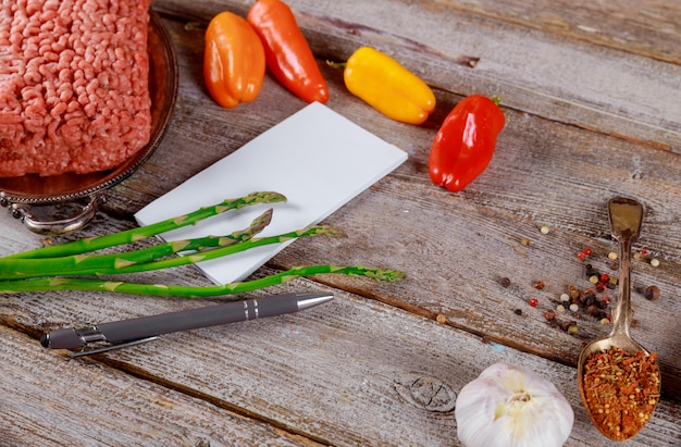Wołowina mielona z przyprawami i warzywami, kolorowa papryka i szparagi, notatnik, długopis