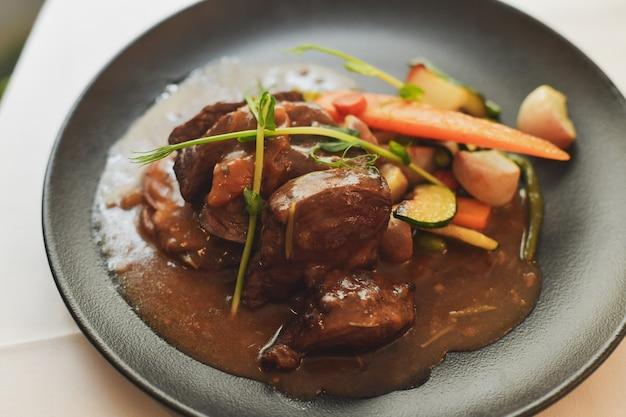 Wołowina po burgundzku z warzywami w czarnym talerzu