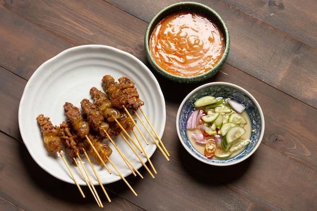 Wołowina satay z grilla i pikantnym sosem orzechowym na podłoże drewniane.