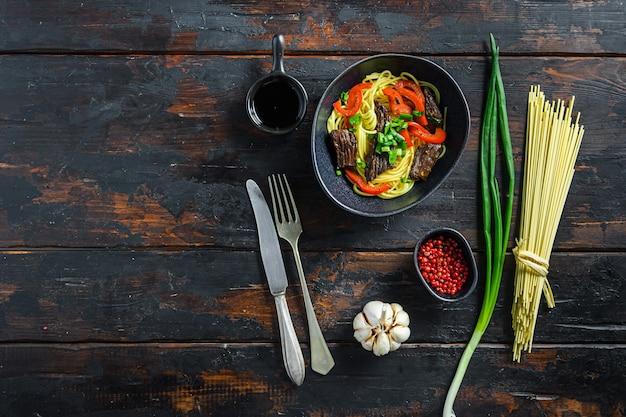 Wołowina stir fry z makaronem w widoku z góry czarnej miski na starym drewnianym stole