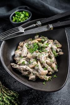 Wołowina stroganoff z pieczarkami i świeżą pietruszką w talerzu na czarnym stole.