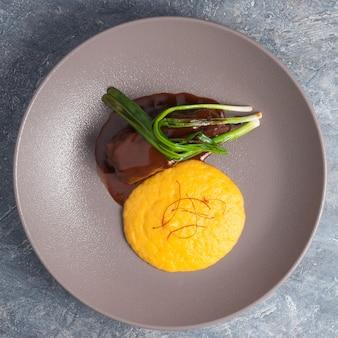 Wołowina w sosie z zieloną cebulką i przystawką kremu kukurydzianego. widok z góry