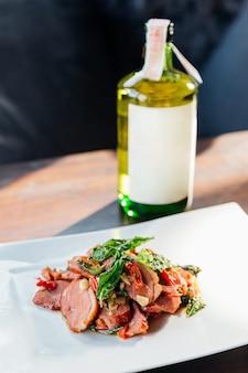 Wołowina wagyu smażona z bazylią, czosnkiem i chili. podawane z japońskim sake. japońskie składniki w tajskim jedzeniu. asian fusion food.