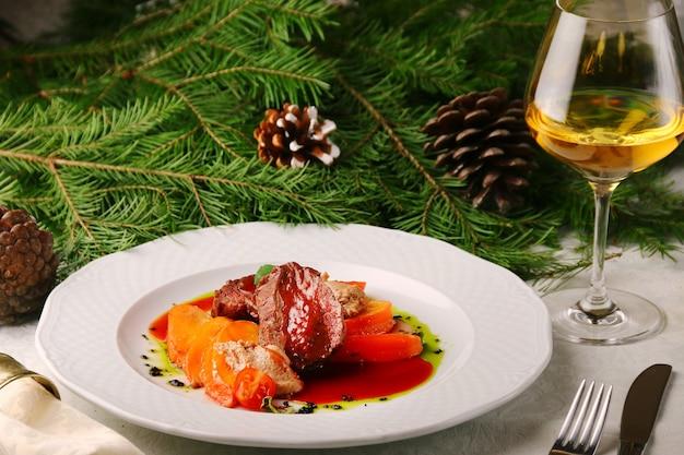 Wołowina z persimmonem i kieliszkiem białego wina na choince. mięso nadziewane owocami.