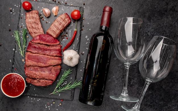 Wołowina zajączek, butelka wina i okulary na kamiennym tle. koncepcja obchodów wielkanocnych