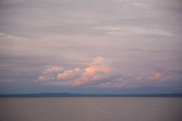 Wolumetryczne różowe i niebieskie chmury o zachodzie słońca nad górami i wodą