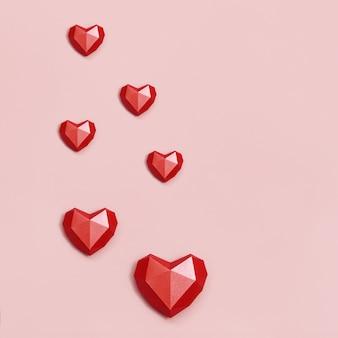Wolumetryczne serca papierowe w kolorze czerwonym. kartkę z życzeniami lub zaproszenie na kartę ślubu lub walentynki.