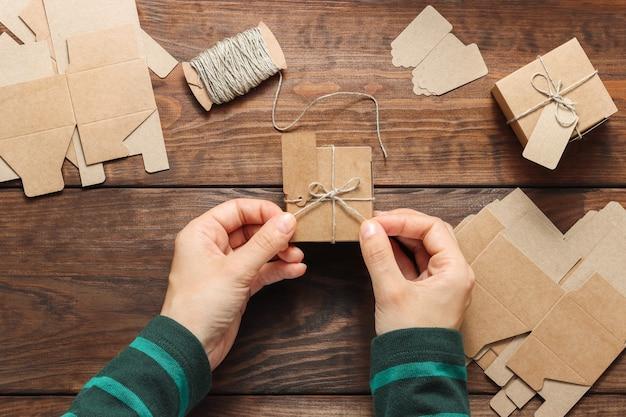 Womans ręce owijają pudełko w wstążkę sznurka