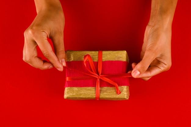 Womans ręce trzymając prezent lub obecne pudełko, widok z góry na czerwonym tle.