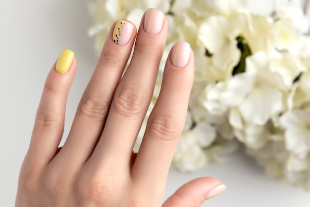 Womans ręce z wiosenno-letnim wzorem paznokci. modny modny kobiecy manicure w minimalistycznym stylu. szablon salonu piękności