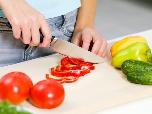 Womans ręcznie krojenie warzyw na biurku w kuchni