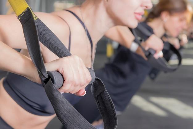 Womans ręcznie trenuje na siłowni, robi ćwiczenia fitness z pętlą z paskami
