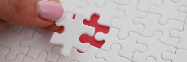 Womans ręcznie umieszcza ostatni kawałek układanki na stole zbliżenie. rozwiązywanie problemu biznesowego