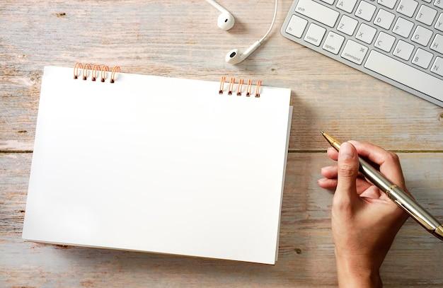 Womans ręka robi coś na pusty notatnik strona klawiatura notatnikkreatywne biurko.