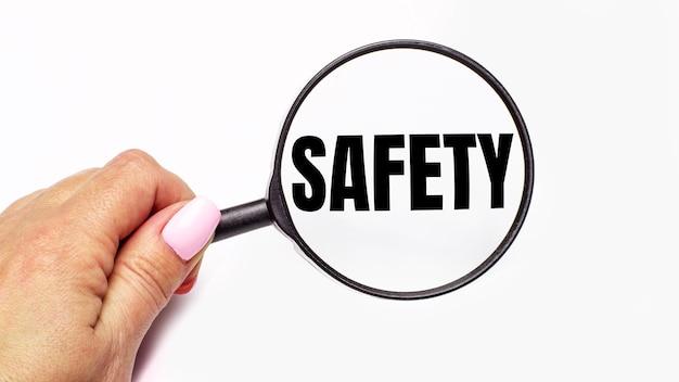Womans ręka trzyma lupę z napisem bezpieczeństwo