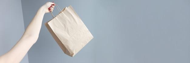 Womans ręka trzyma papierową torbę na zakupy zbliżenie close