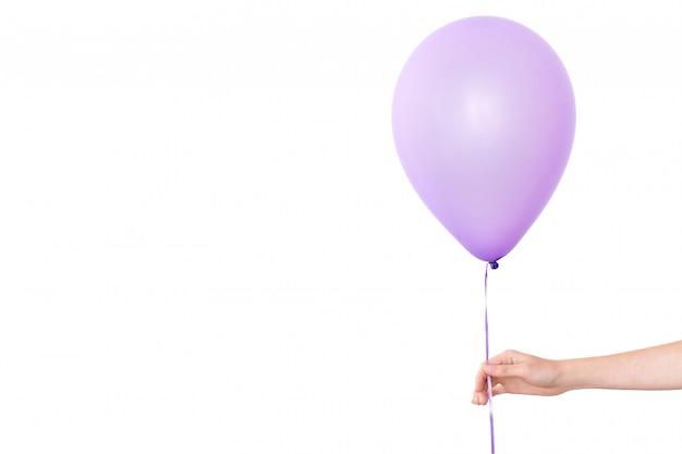 Womans ręka trzyma purpury balonu bielu tło