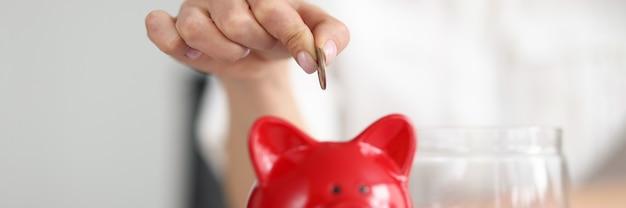 Womans ręka umieszczająca monetę w skarbonce zbliżenie oszczędzanie pieniędzy koncepcja