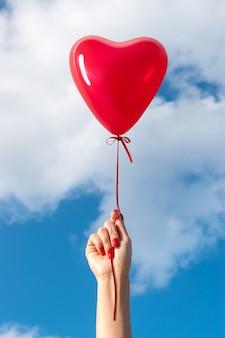 Womans ręka z balonem w kształcie serca na tle nieba.