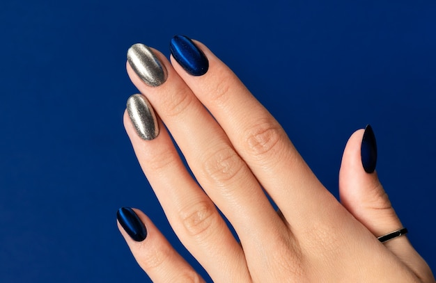 Womans ręka z blaskiem modny manicure na niebieskim tle. party dark night silver nail design.